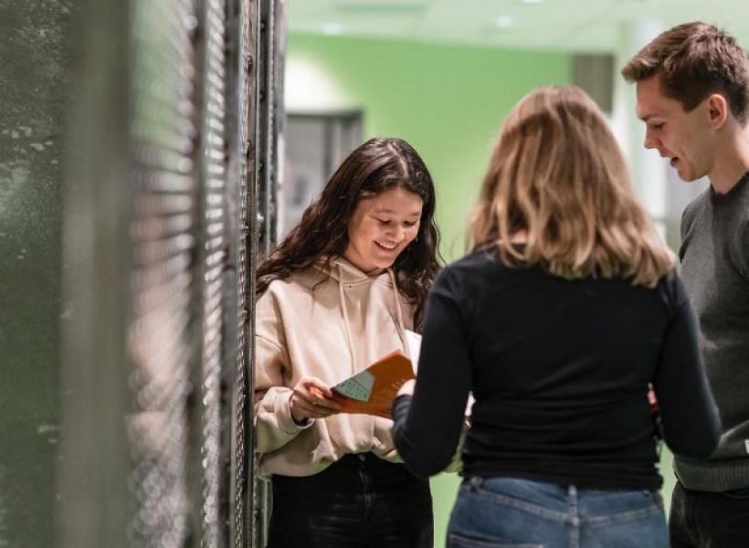 Tre elever i en skolkorridor.